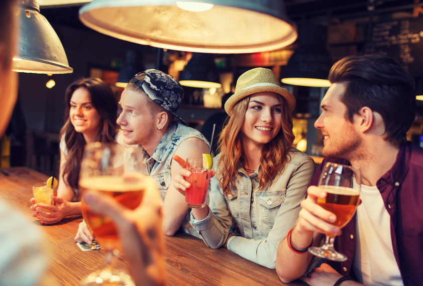 Students with drinks talking at bar in Jesmond